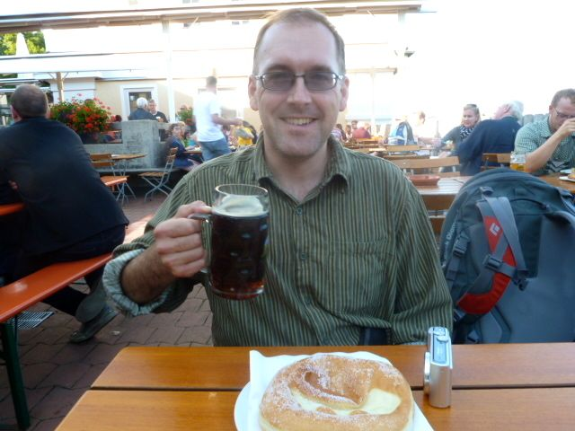 My friend enjoying a pint of the famous Andechser Doppelbock Dunkel and a Bavarian donut.