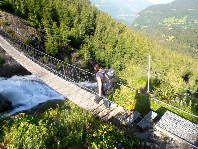 adventure travel blogger Laurel Robbins crossing a bridge while hiking the Tour du Mont Blanc.