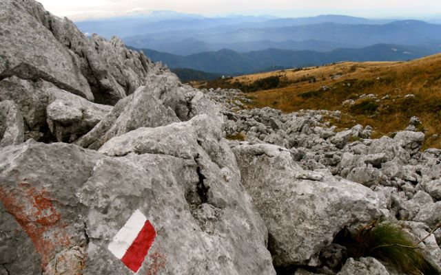Trail marker on a rocky outcrop near the summit of Monte Matajur