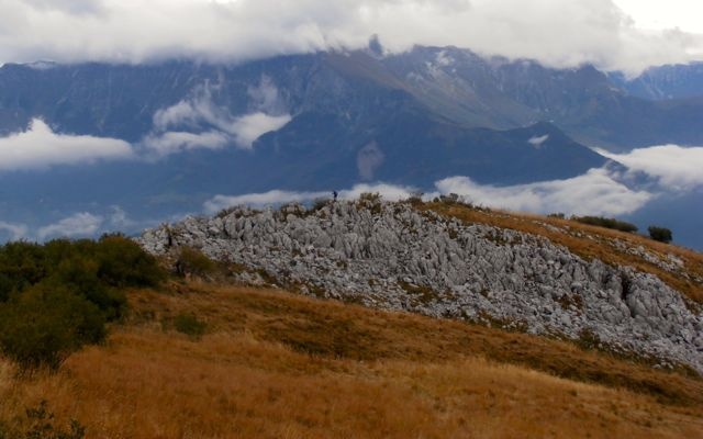 Hiker on a rocky outcrop with the Julian Alps in the background.
