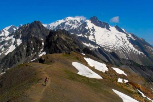 a hiker on one of the two highest points of the Tour du Mont Blanc