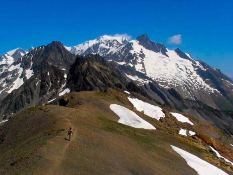 a hiker trekking on one of the two highest points of the Tour du Mont Blanc