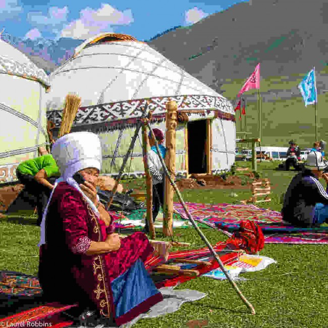 Kyrgyz woman sitting in front of a yurt at the World Nomad Games