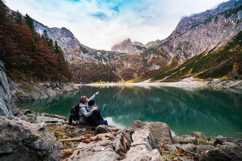 Couple enjoying lake and mountain views while hiking.