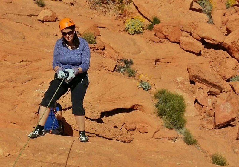 Adventure travel blogger Laurel Robbins rapelling.