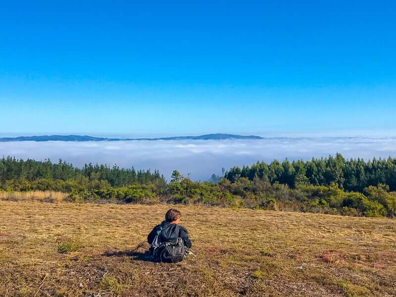 walker resting to enjoy the clouds and far-reaching views on the Camino de Santiago