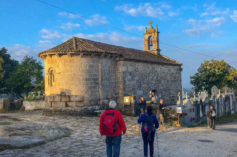 Pilgrims looking at a church on the Camino de Santiago, the last 100 km