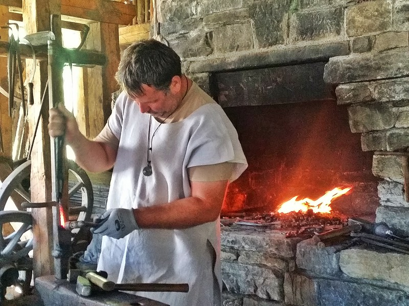 A Burgbau blacksmith using only medieval tools and techniques to build the castle near the medieval village of Freisach in Carinthia.