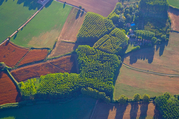 A boot shaped patchwork farm seen while hot air ballooning over Costa Brava, Catalunya, Spain.