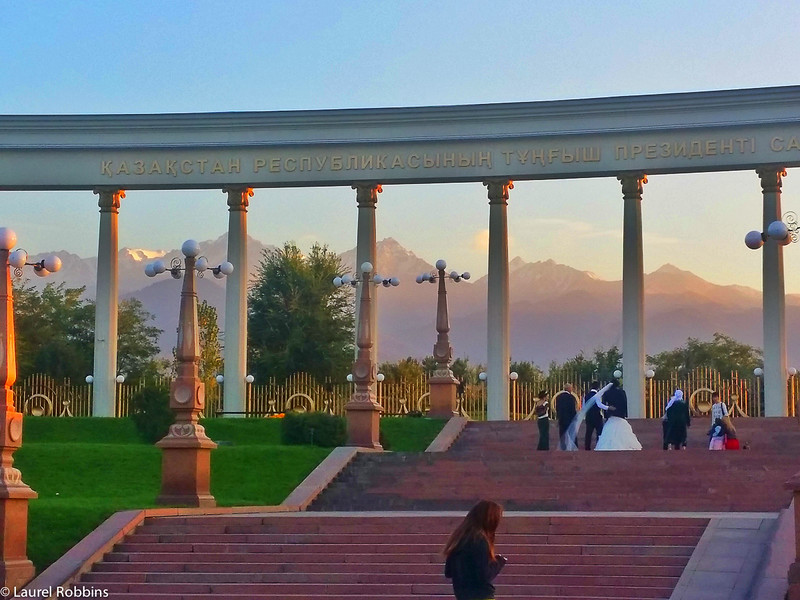 First Presiden'ts Park in Almaty Kazakhstan. Shown is a bride and groom getting their wedding photos done with the Tien Shan mountains as the backdrop.