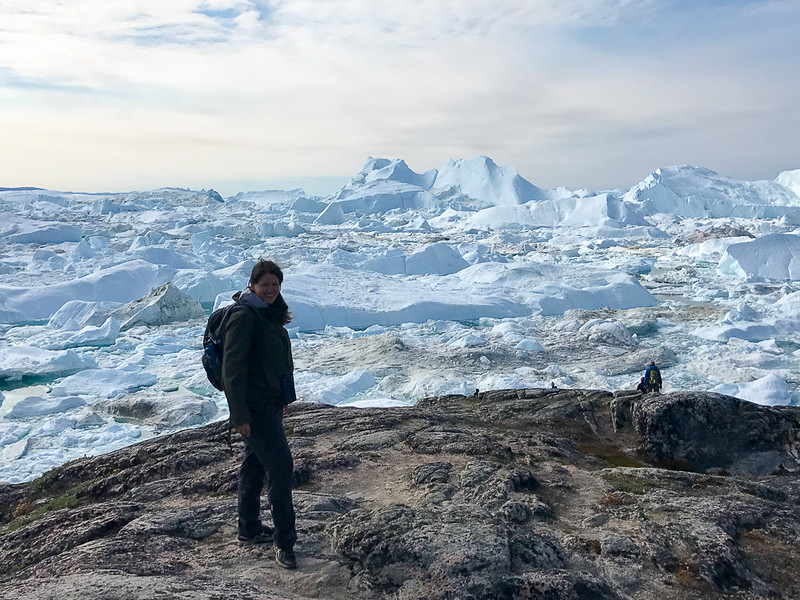 Adventure travel blogger Laurel Robbins in front of the Ilulissat Icefjord in Greeland.