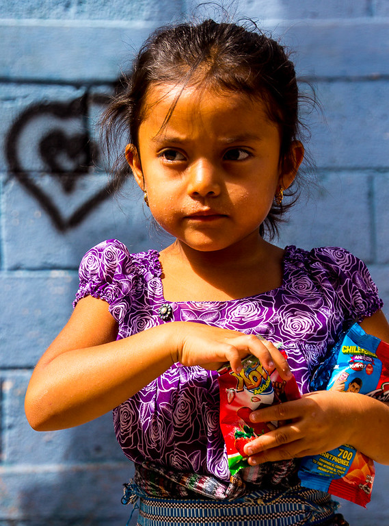 Young Guatemalan girl eating a snack on a school break.