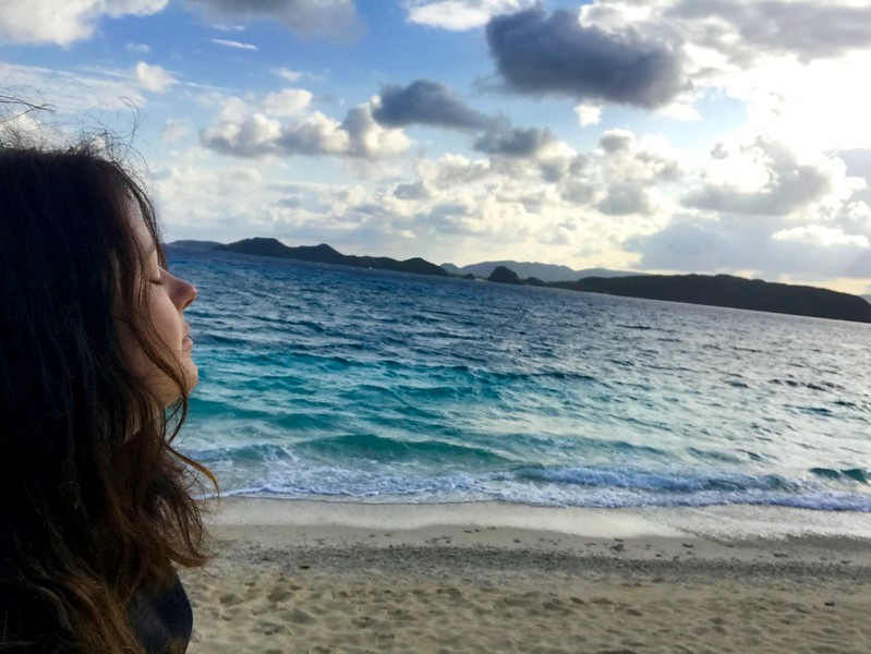 Adventure travel blogger Laurel Robbins enjoying the ocean breeze on Aka Island in Okinawa, Japan.