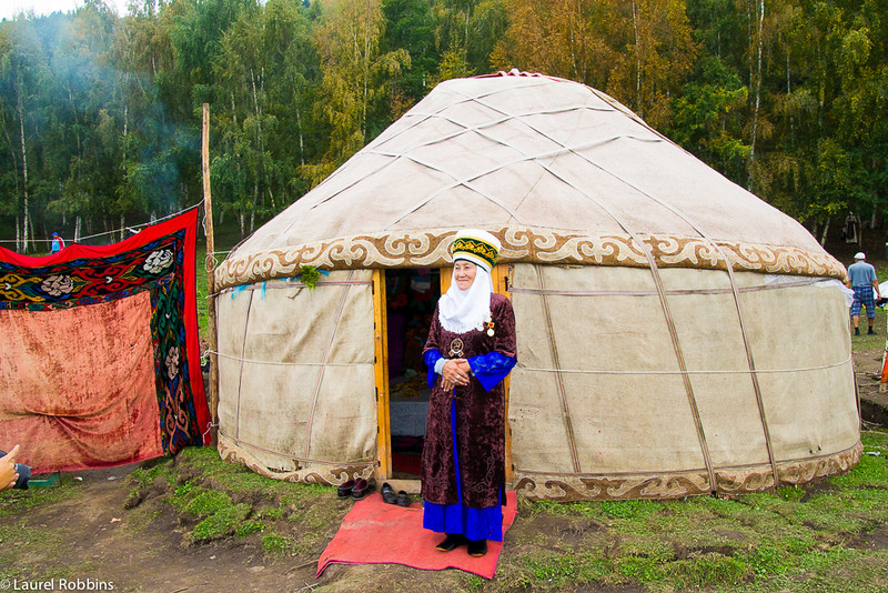 Kyrgyz woman standing in front of her yurt.