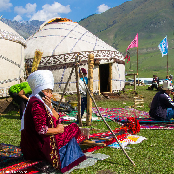 Kyrgyz woman on her mobile phone while weaving at the World Nomad Games