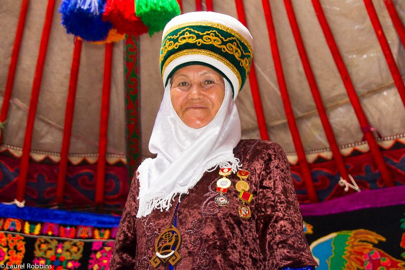 A Kyrgyz woman in traditional nomadic clothing inside her yurt.