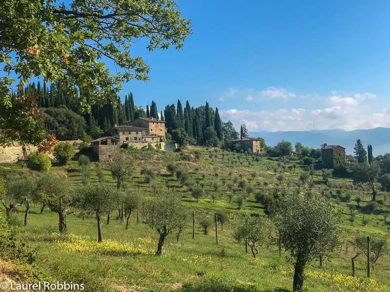 Hikers pass by orchards and farmhouses on the Path of Gods Italy in Tuscany.