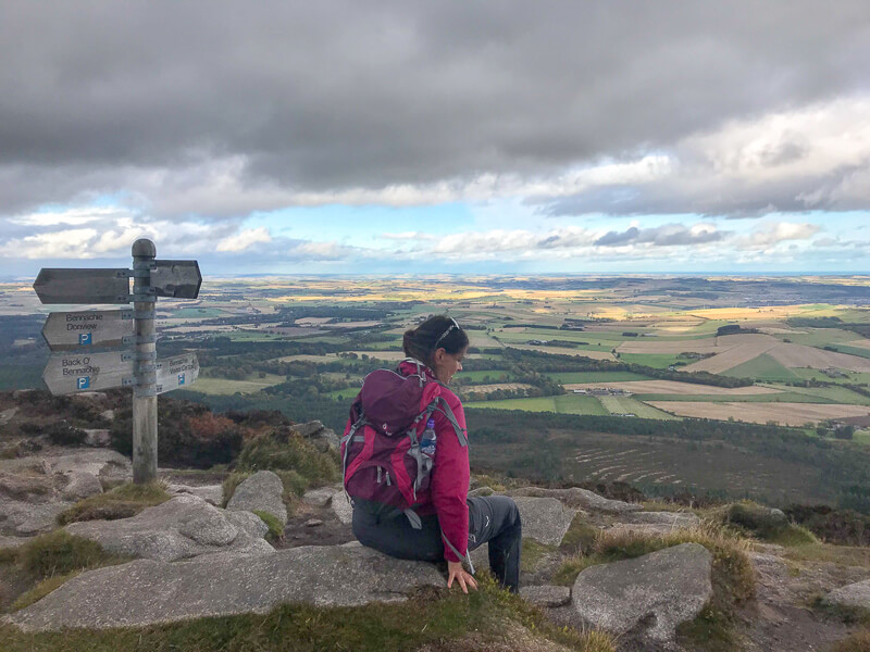 Hiker at the top of Oxen Craig in Bennachie enjoying the views