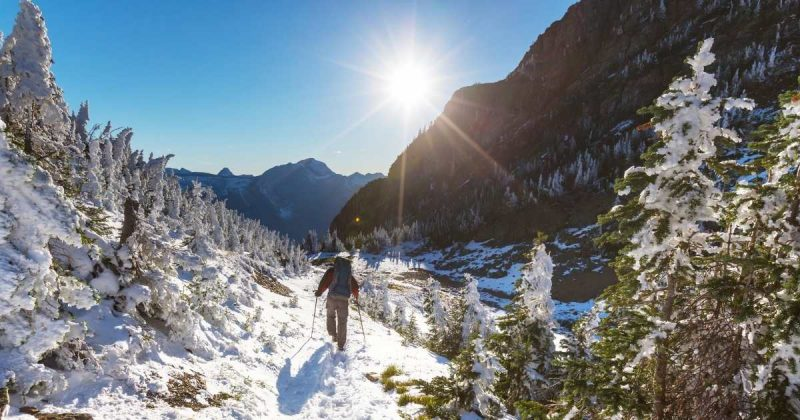 hiker on a snow-covered winter trail with mountains in the background