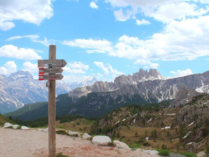 Hiking route signs with the Dolomites Mountain Range on the Alta Via 1 South