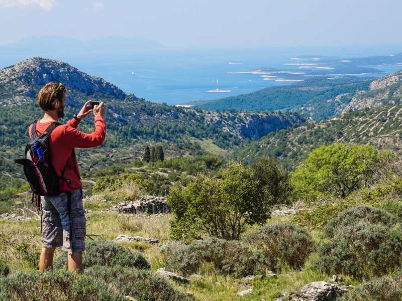 male hiker taking a view of Croata's landscape and the Adriatic Sea