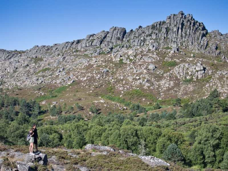 Hikers admiring the rock formations in Geres, Portugal