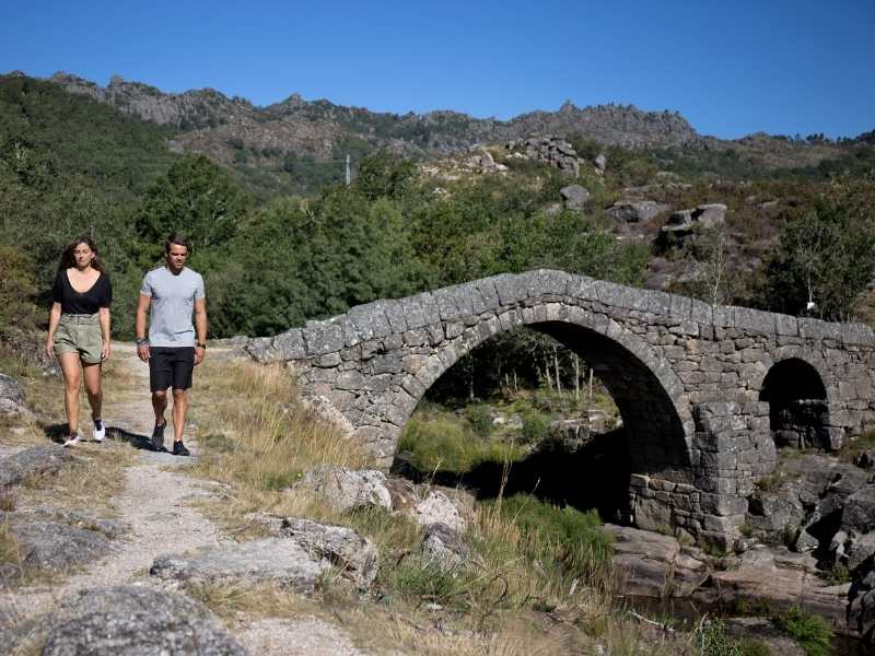 Couple hiking near ancient bridge in Peneda-Geres, Portugal